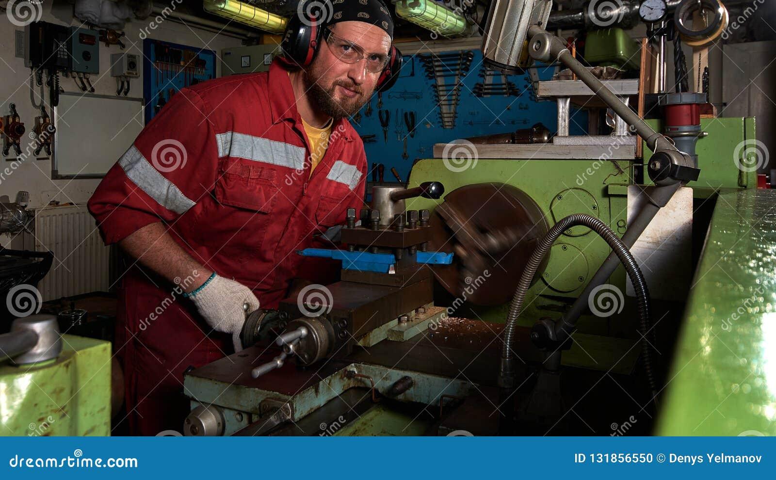 Arbetare i den röda likformign som fungerar i manuell drejbänk i stort seminarium för metall