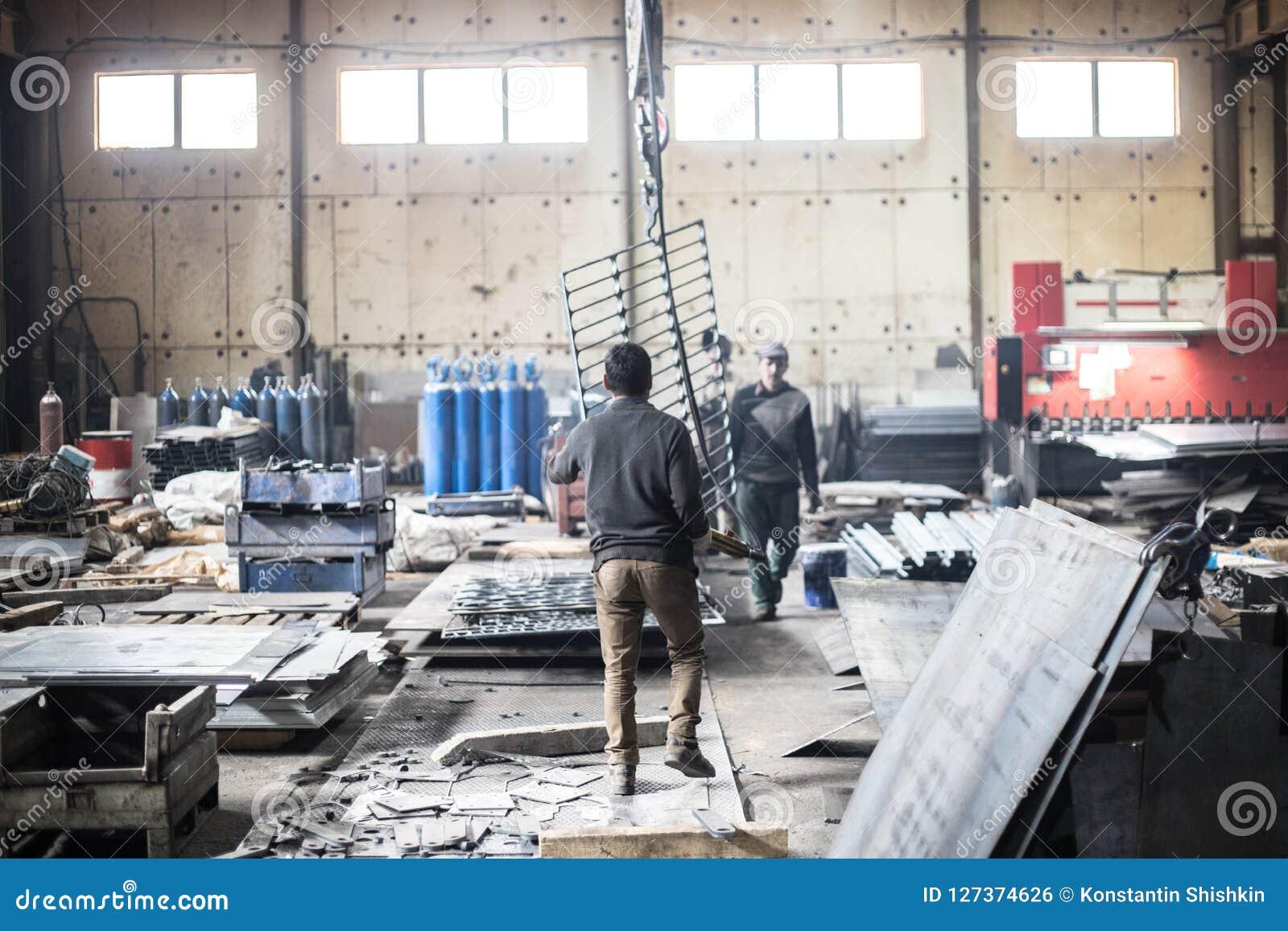 Arbetare i kängor går inom den industriella fabriken