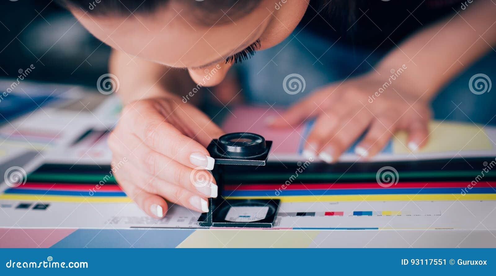 Arbetare i printing och centar bruk för press ett förstoringsglas