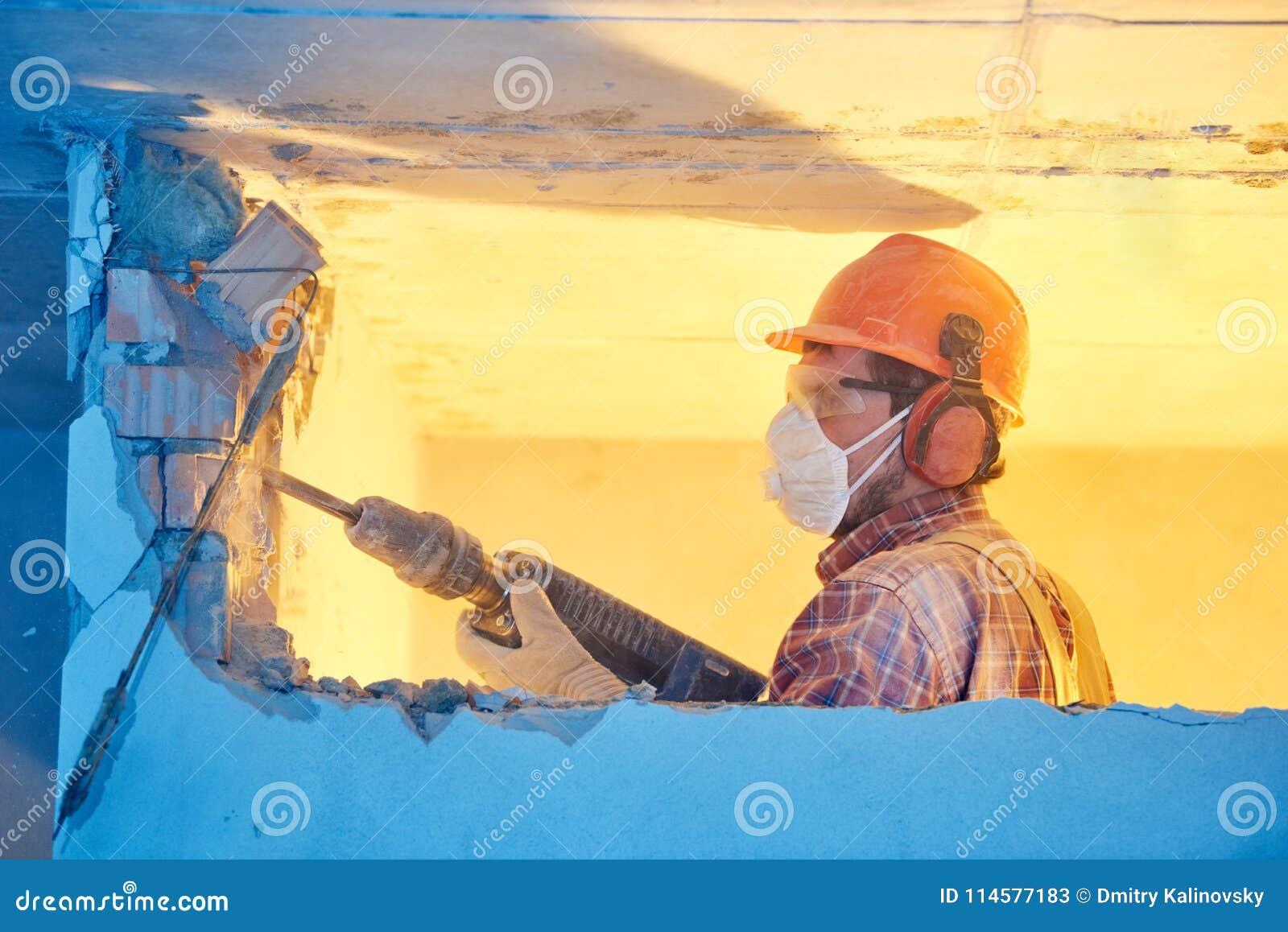 Arbetare med rivninghammaren som bryter innerväggen