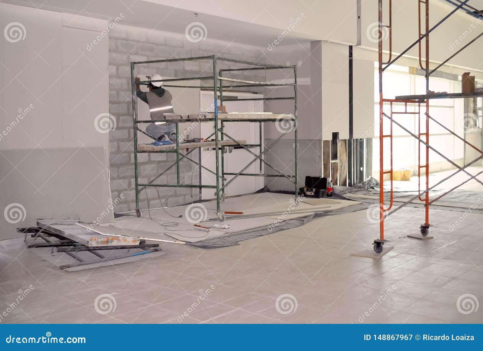 Arbetare på materialet till byggnadsställning som installerar gipsväggen