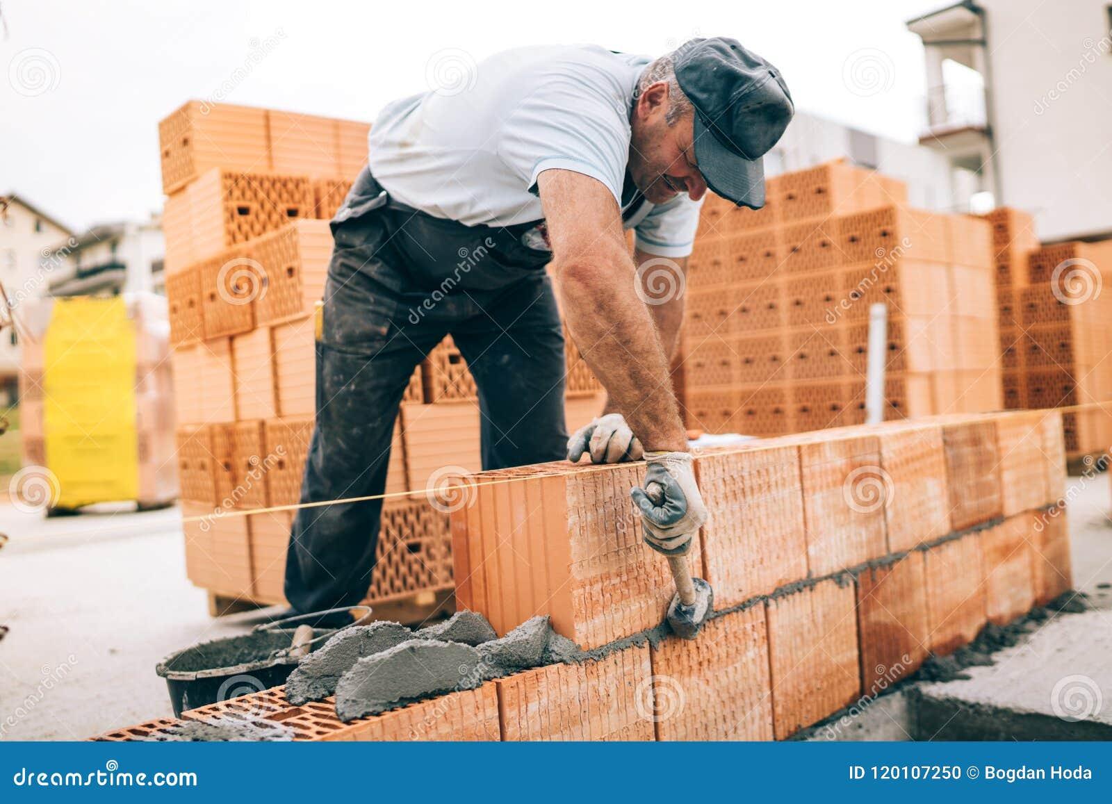 Arbetare som bygger yttre väggar, genom att använda hammaren för att lägga tegelstenar i cement Detalj av arbetaren med hjälpmede