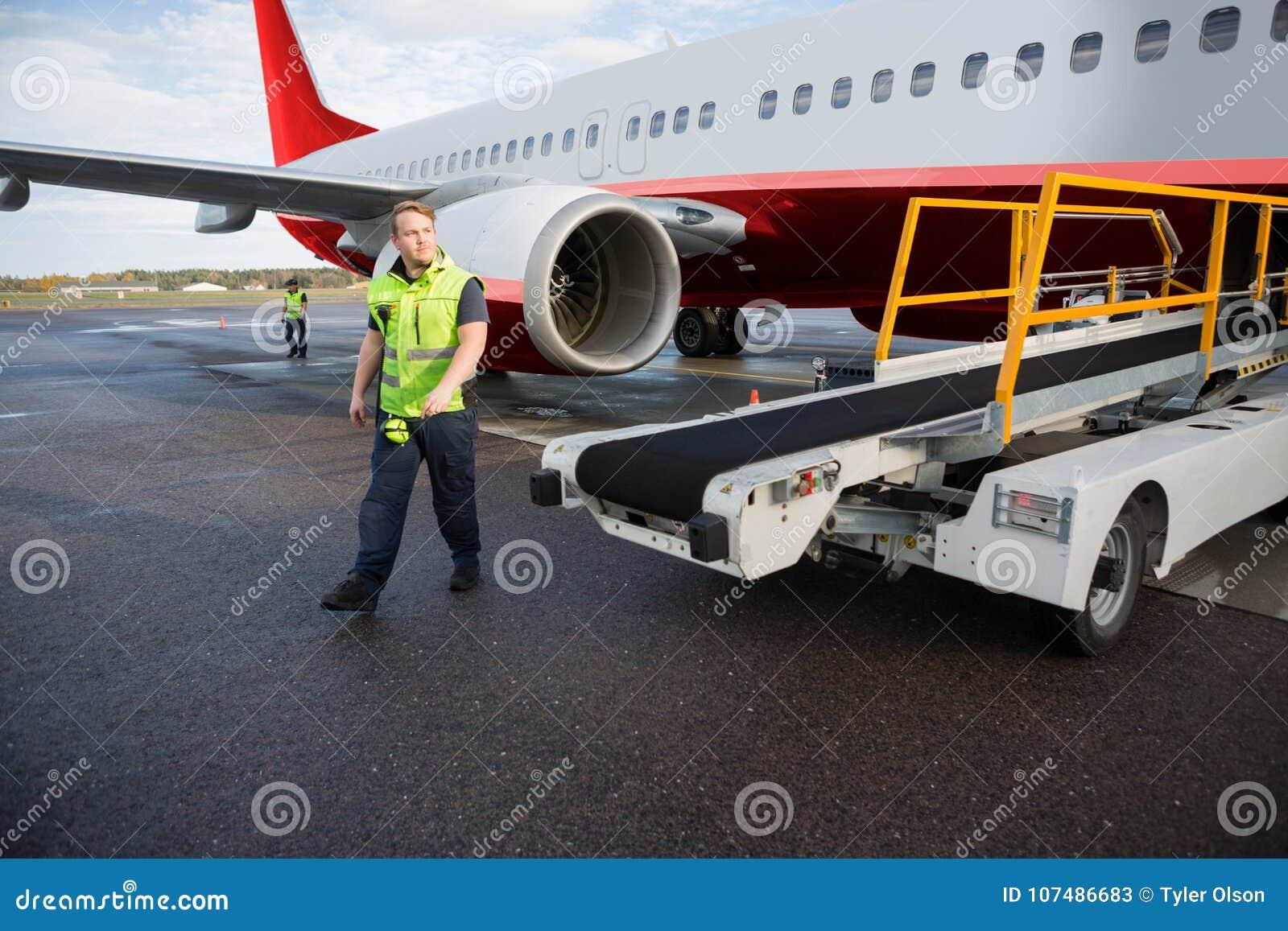 Arbetare som går med transportörlastbilen med flygplanet på landningsbana