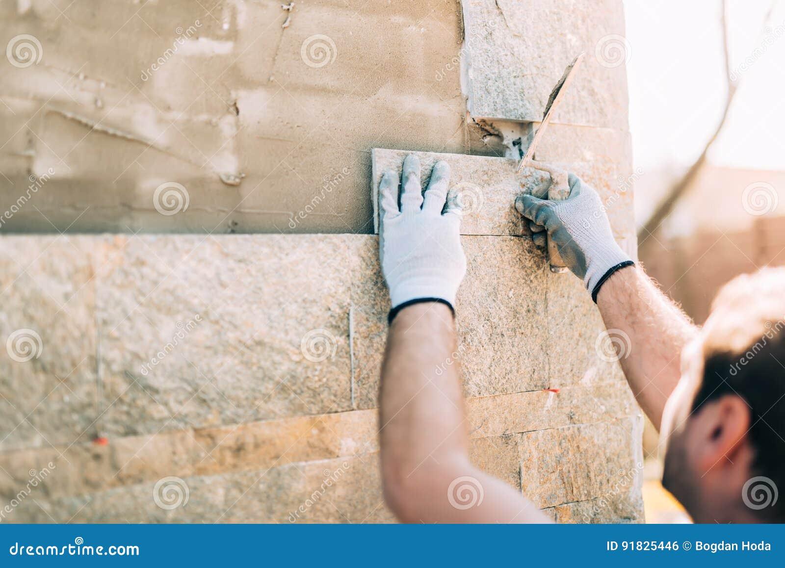 Arbetare som installerar stentegelplattor på väggen på konstruktionsplats