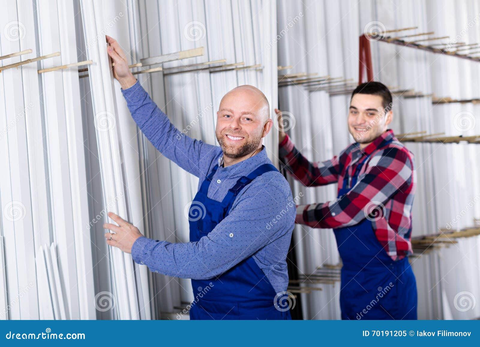 Arbetare som kontrollerar fönsterramar
