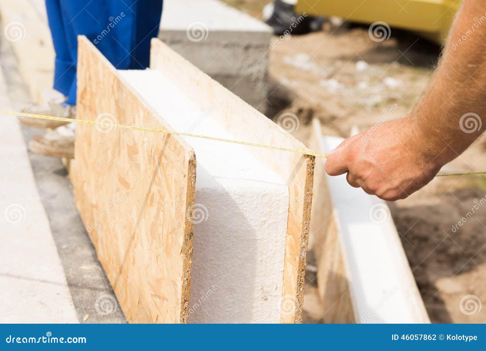 Arbetare som mäter en monteringshusväggpanel