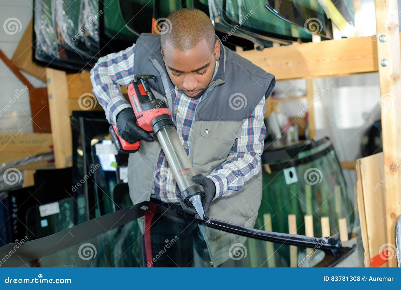 Arbetare som sätter lim på exponeringsglas