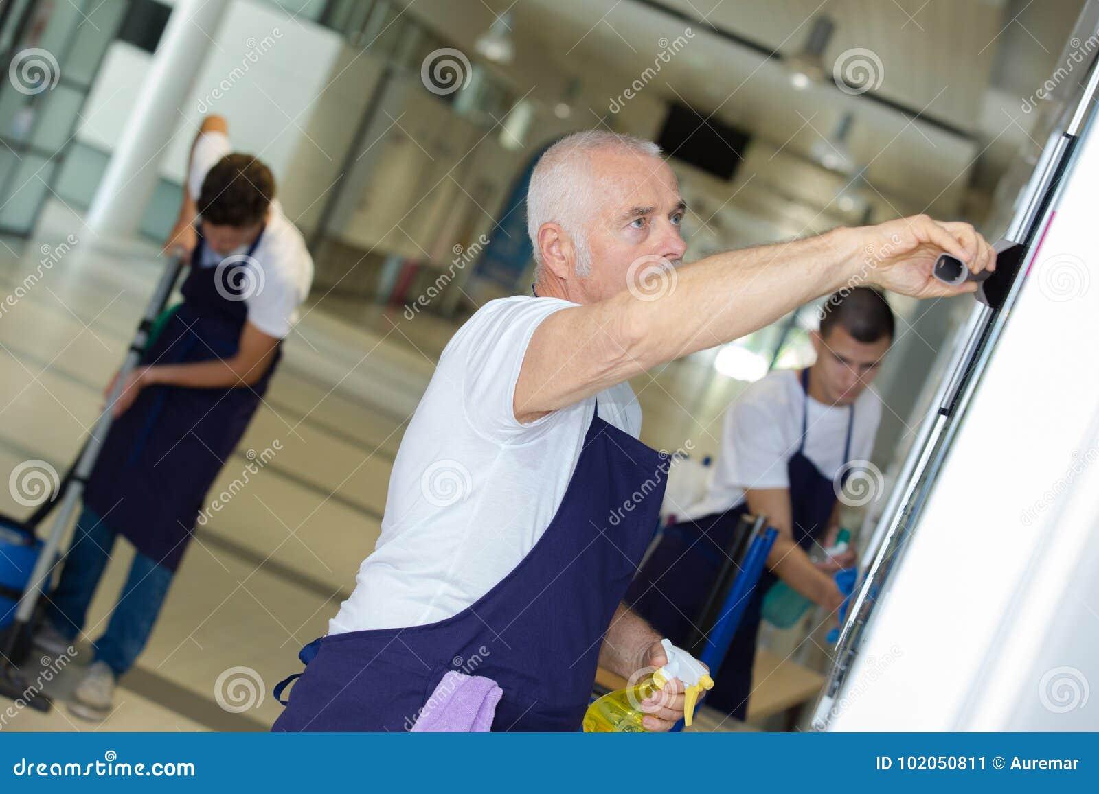 Arbetare som tvättar golvbyggnad