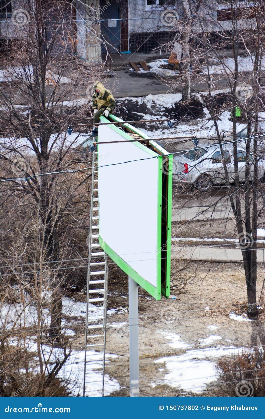 Arbetaren f?rbereder affischtavlan till installation av den nya annonseringen Industriell klättrare som arbetar på en stege - för