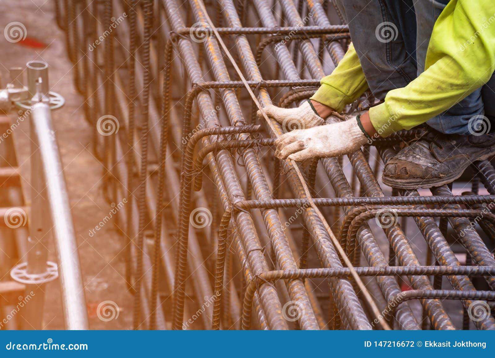 Arbetaren satte den gr?na s?kerhetsskjortan, anv?nder ett mjukt j?rn, binder en stor st?ltr?d i omr?det som bygger en stor byggna