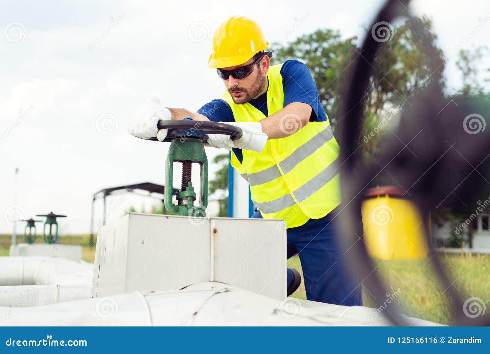 Arbetaren stänger ventilen på den olje- rörledningen