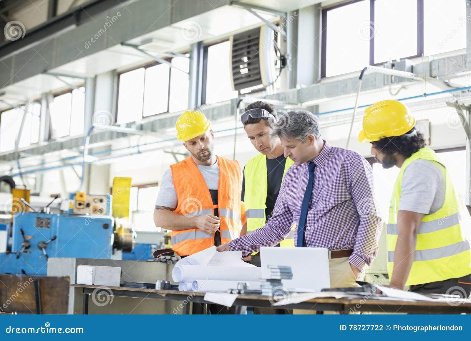 Arbetsledare med arbetare som undersöker ritningar på tabellen i bransch