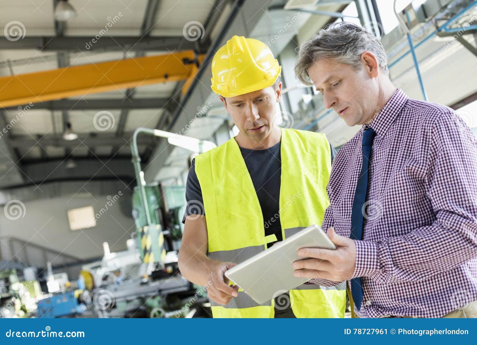 Arbetsledare och manuell arbetare som använder den digitala minnestavlan i metallbransch