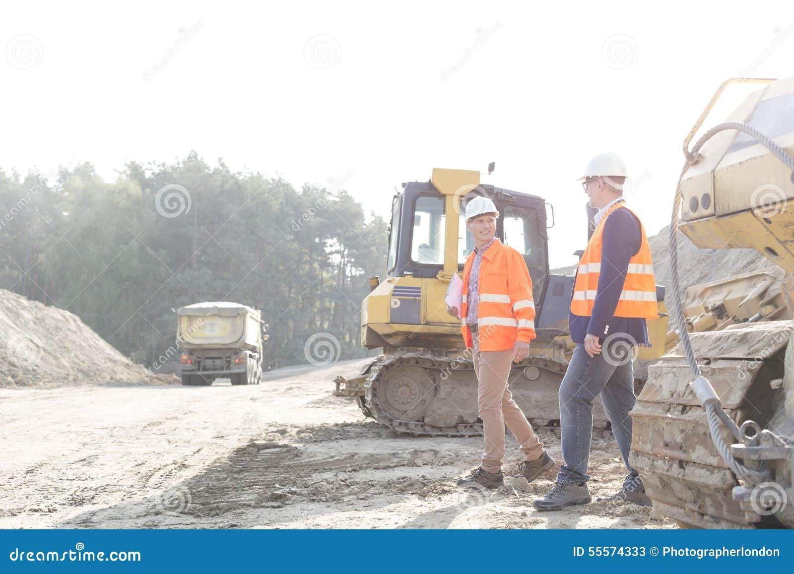 Arbetsledare som går på konstruktionsplatsen mot klar himmel