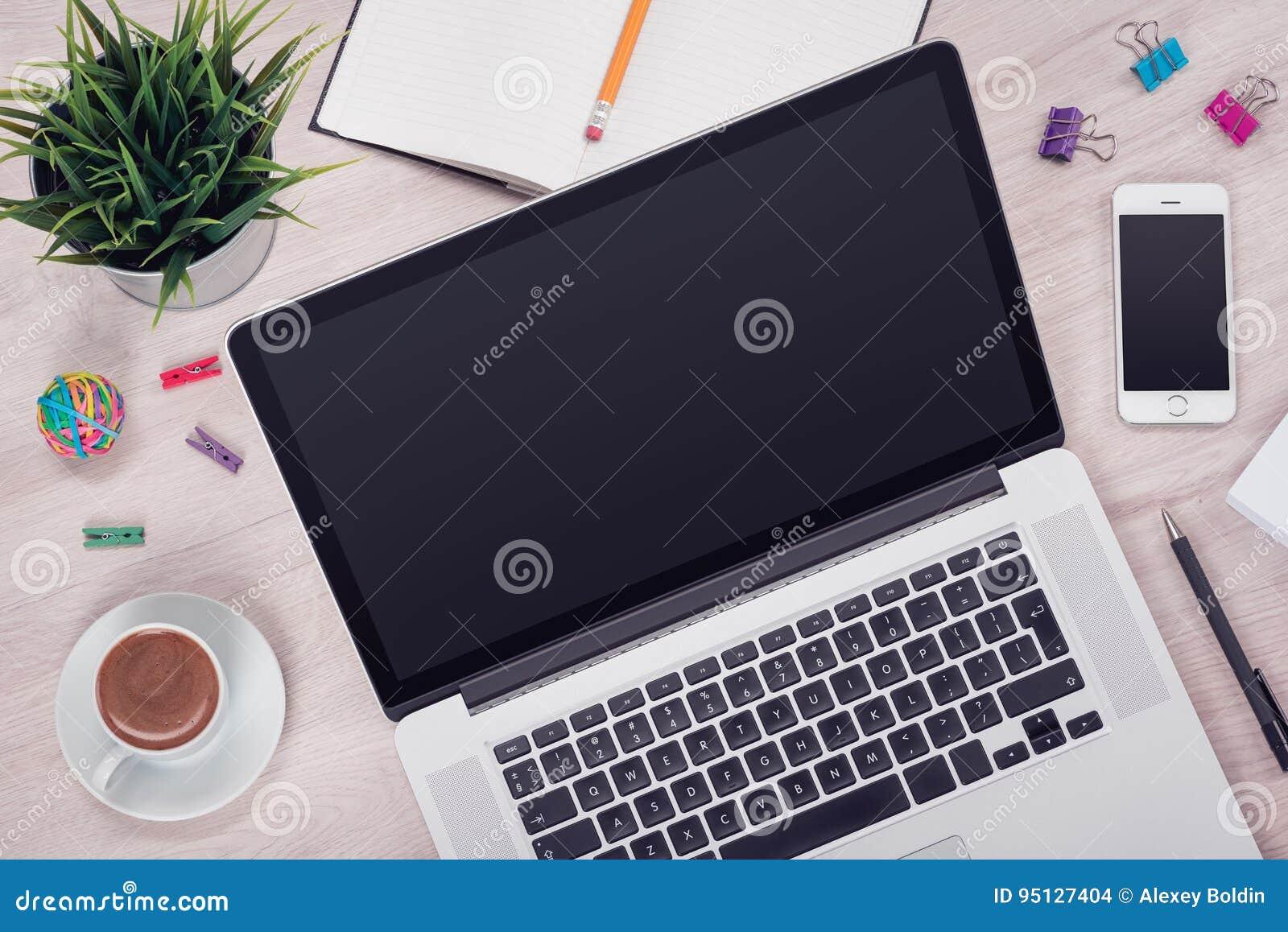 Arbetsplats med den öppna bärbara datorn på den skrivbords- sikten för kontor