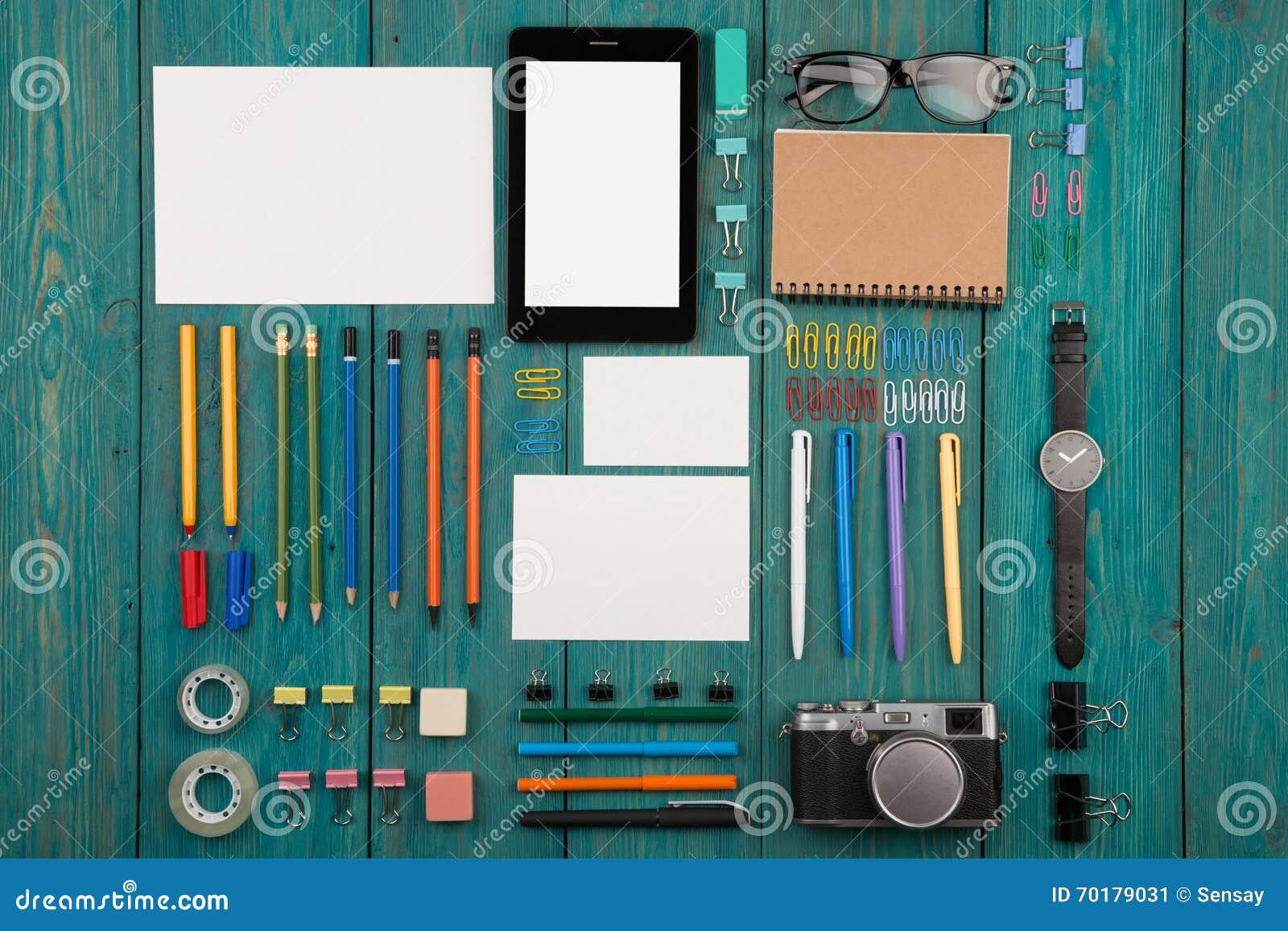 Arbetsplats med minnestavlaPC, kameran, klockan och annan kontorstillförsel