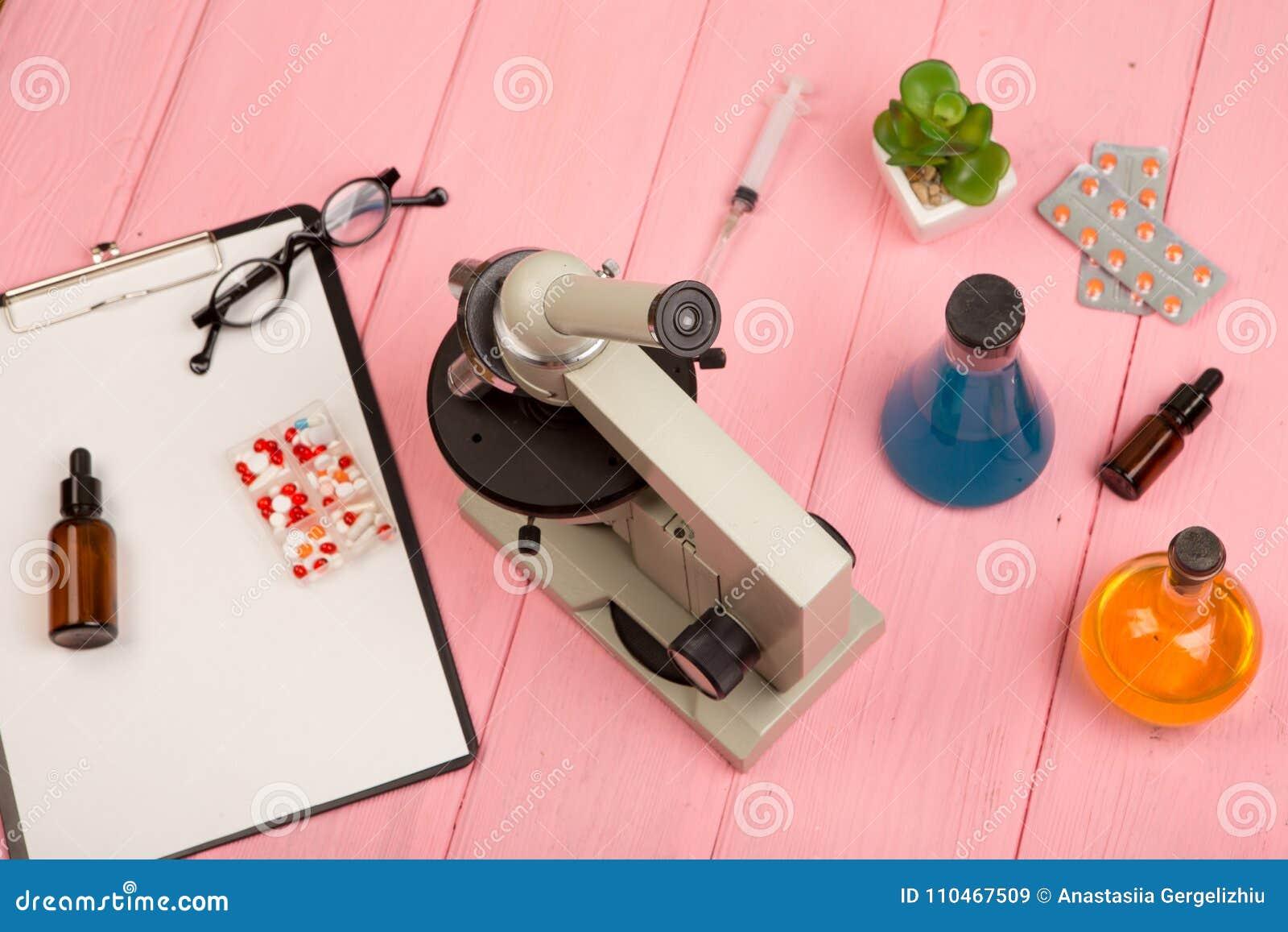 Arbetsplatsforskaredoktor - mikroskop, preventivpillerar, injektionsspruta, glasögon, kemiska flaskor med flytande, skrivplatta p