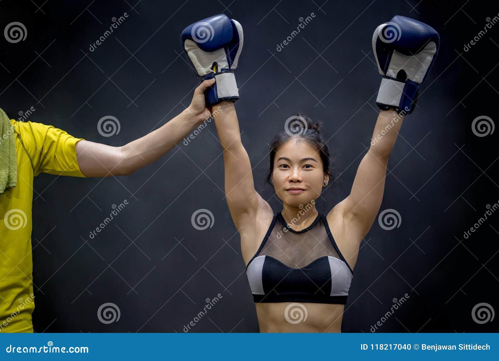 Arbitre la mano femenina de elevación del boxeador, ganador del partido