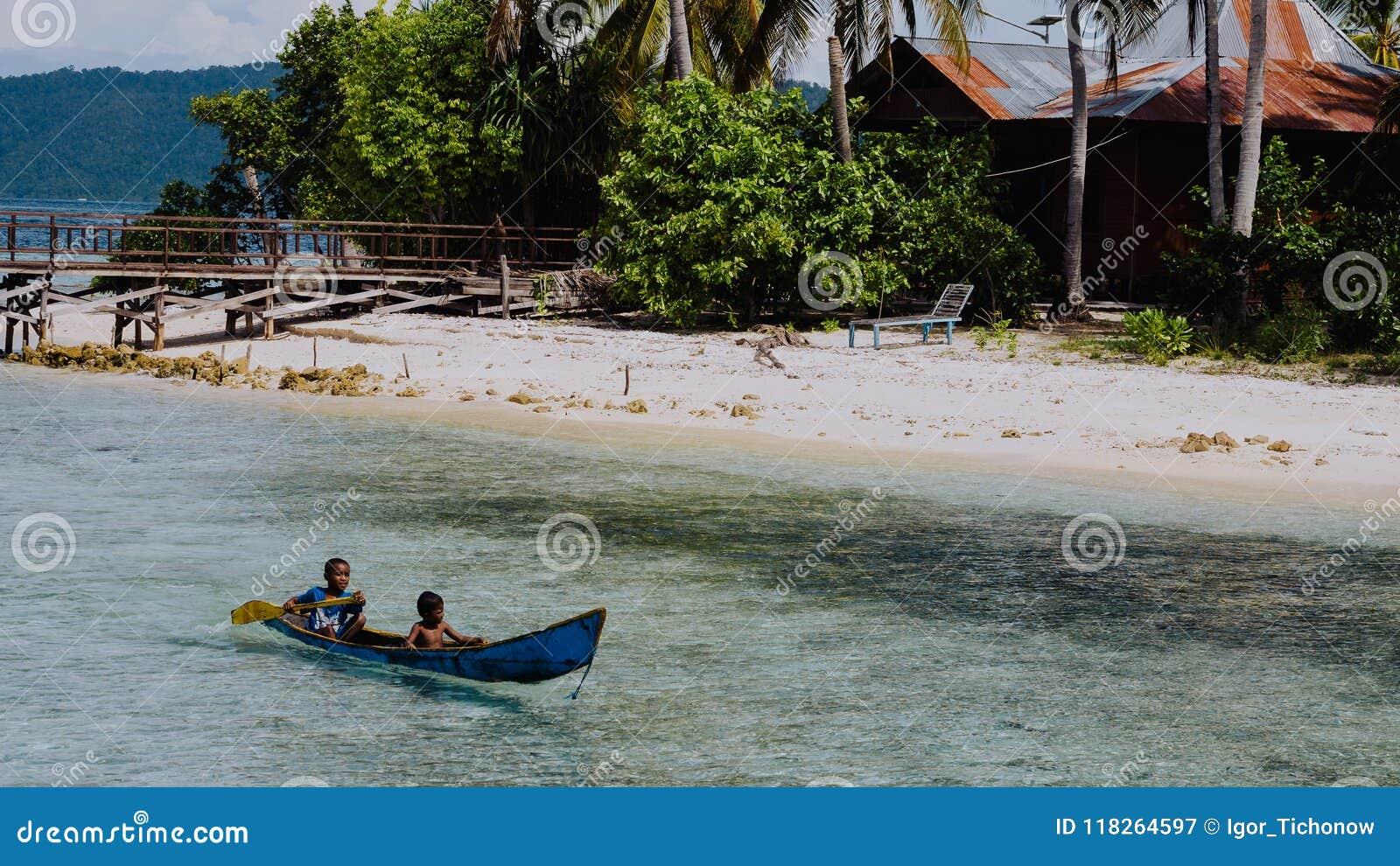 Arborekeiland, Raja Ampat, 10 Oktober, 2016: lokale jonge geitjes in een boot op Arborek-Eiland in Raja Ampat, West-Papoea
