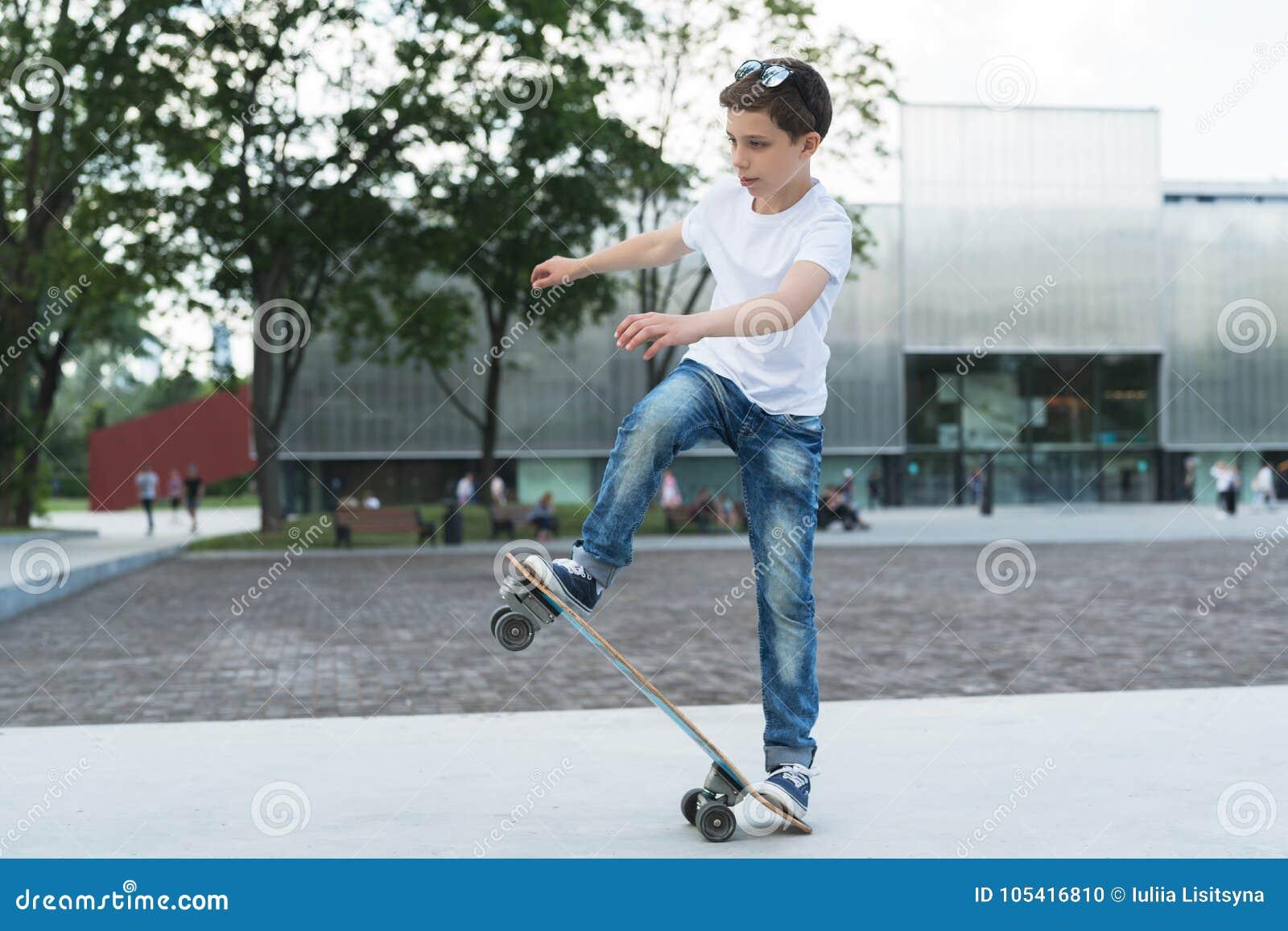 Arbre dans le domaine Le garçon est un adolescent habillé dans un T-shirt blanc et les jeans, patinage, faisant dupe