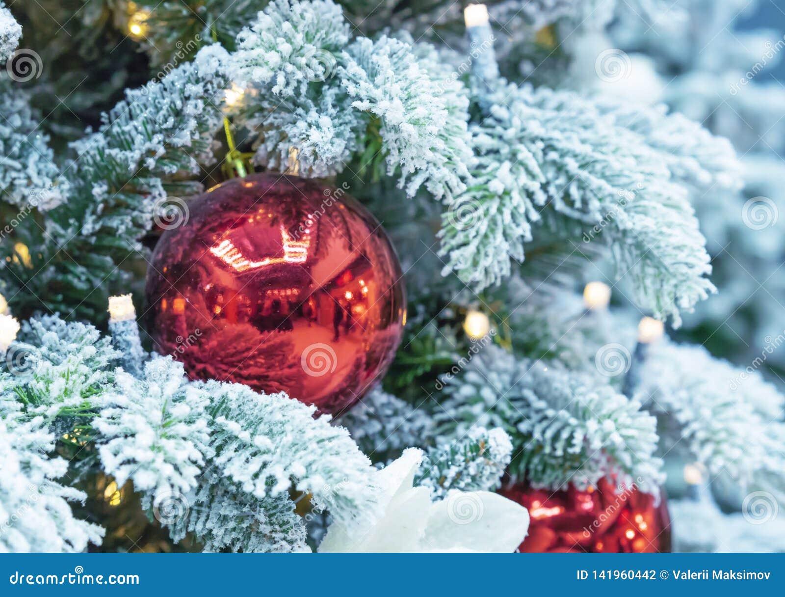 Arbre de Noël couvert de neige décoré des boules rouges et d une guirlande
