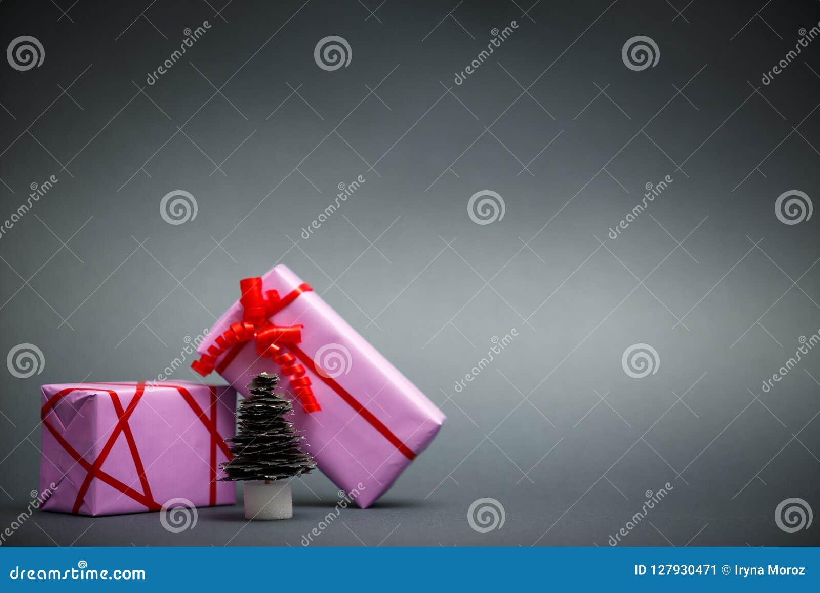 Arbre et cadeaux de Noël de papier sur le fond gris