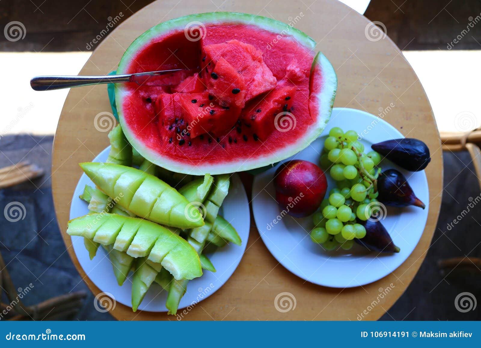 Arbuz, melon i winogrona na trzy talerzach na drewnianym stole,