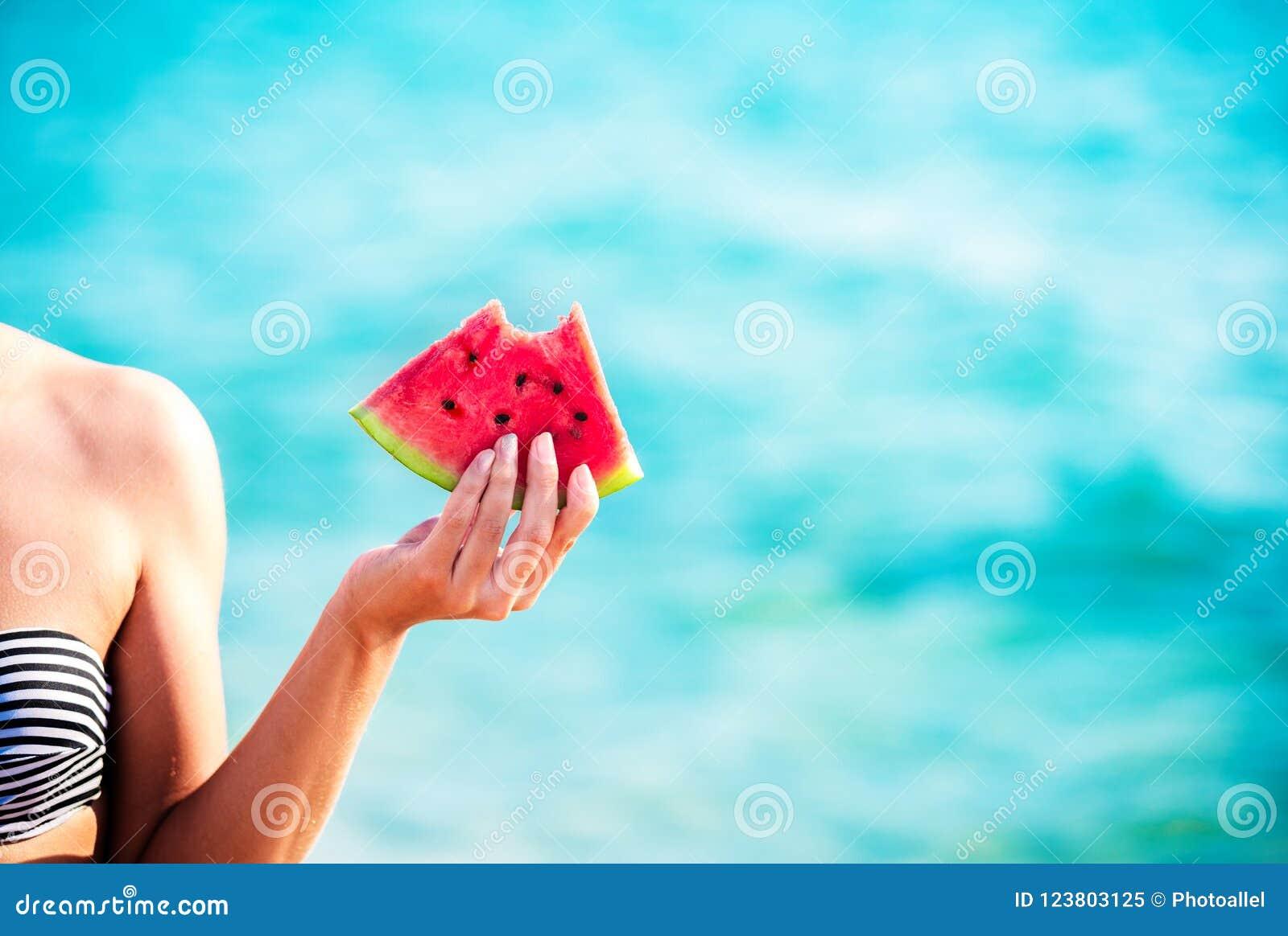 Arbuza plasterek w kobiecie oddawał morze - POV Lata plażowy pojęcie Tropikalnej owoc dieta