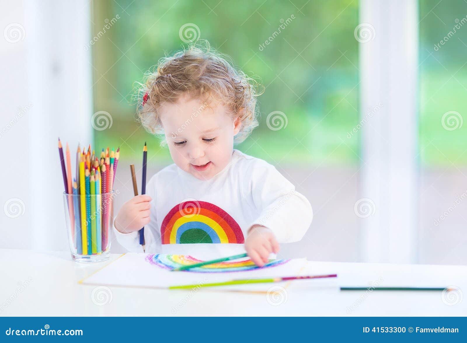 Arc-en-ciel doux de peinture de fille d enfant en bas âge dans la chambre blanche