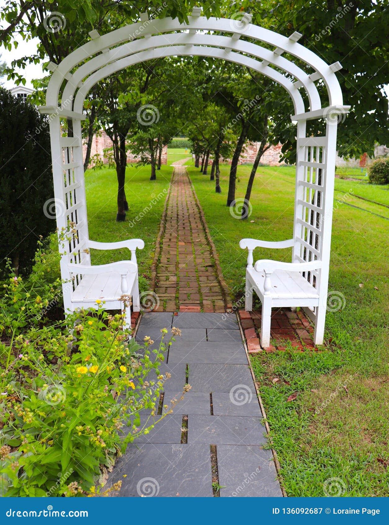 Arcada al aire libre del jardín con los bancos
