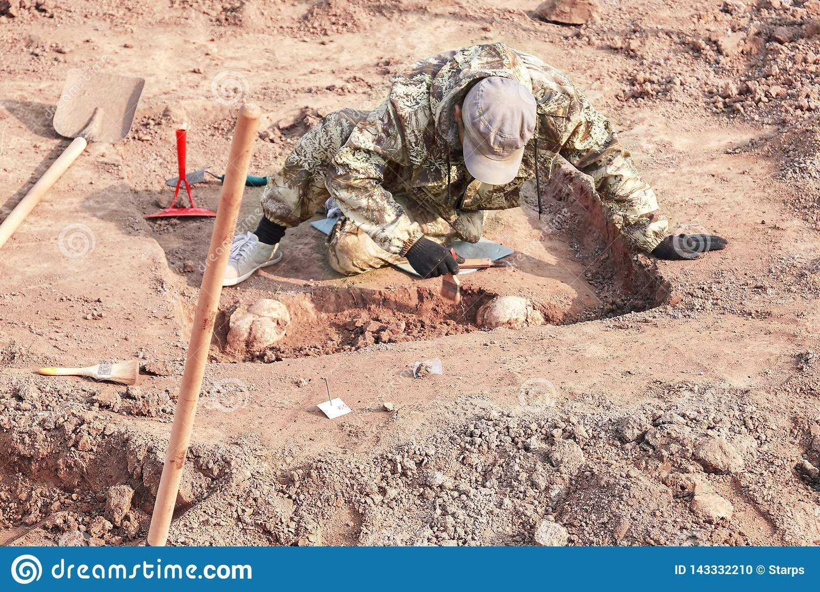 Archaeological excavation. The archaeologist conducting research on human bones, part of skeleton from the ground, with tools sho