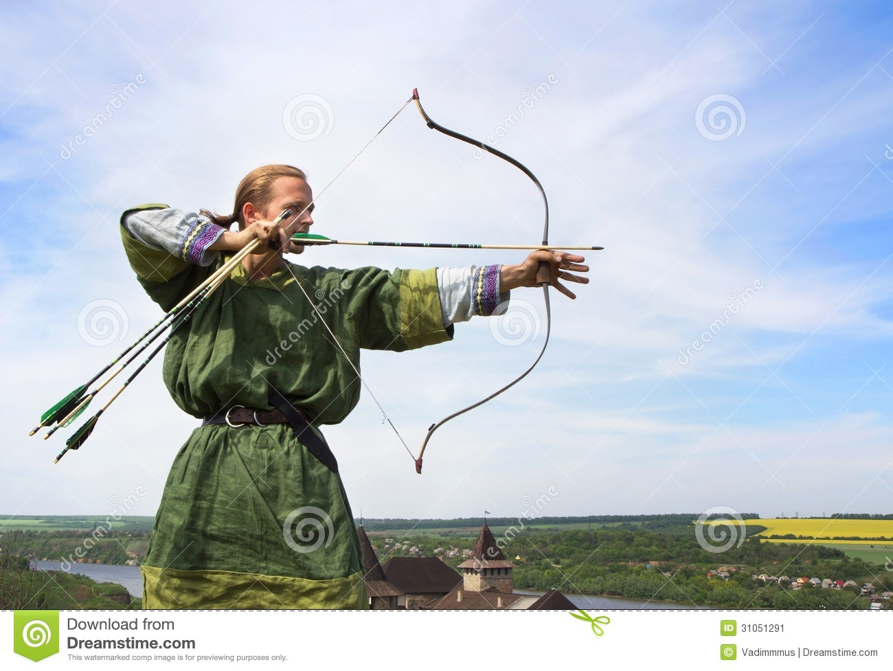 Young archer with bow and arrows in medieval costume aiming.
