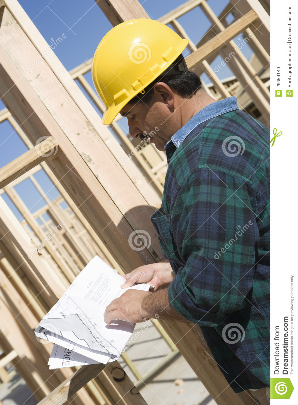 Male architect reading construction plan stock photo for How to read construction site plans