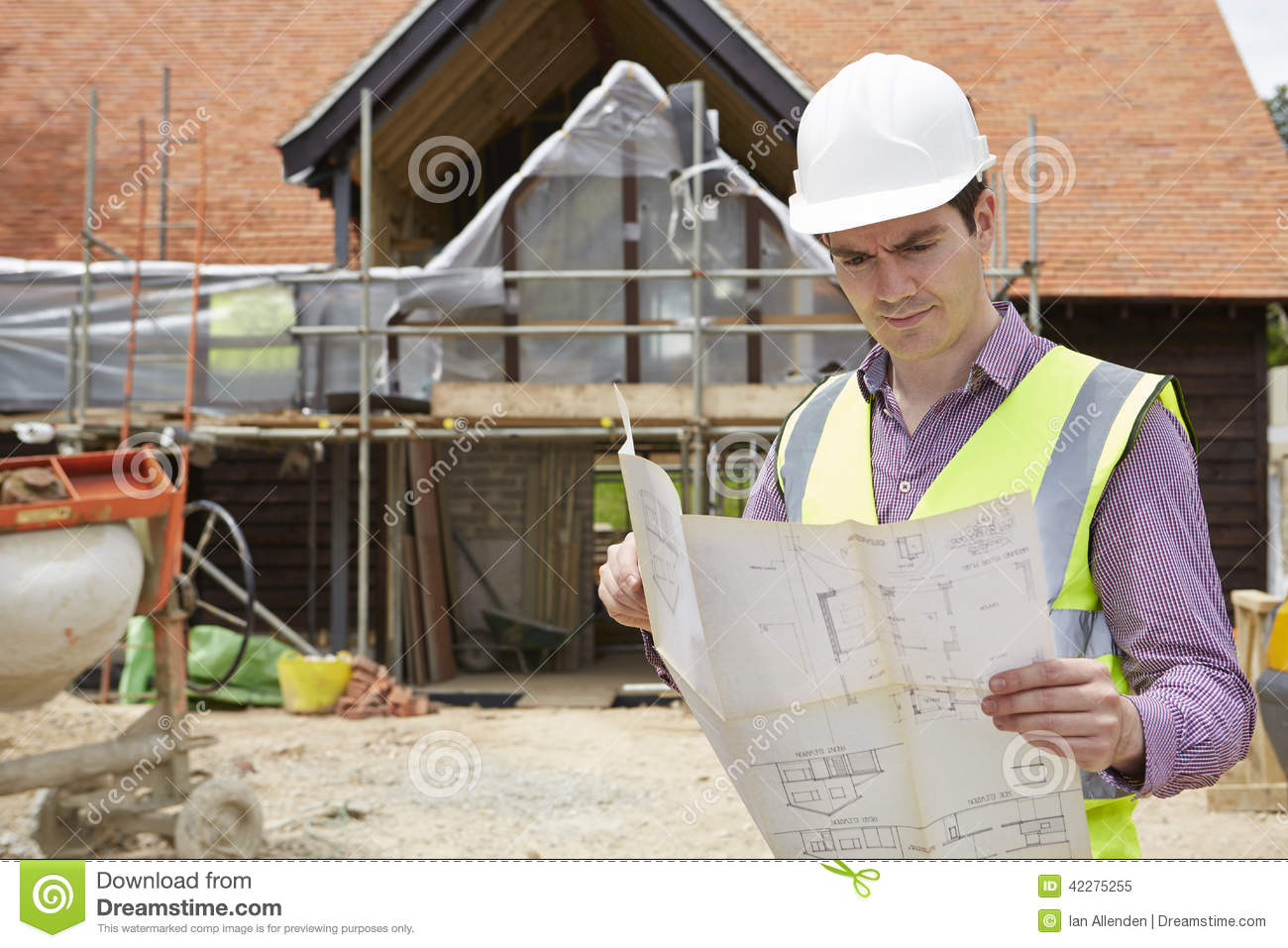 Architect On Building Site Looking At House Plans Stock Photo    Architect On Building Site Looking At House Plans