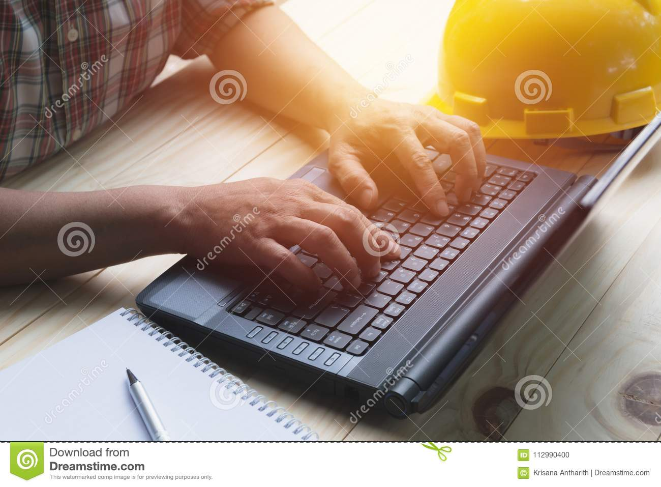 Architect engineer using laptop for working with yellow helmet o