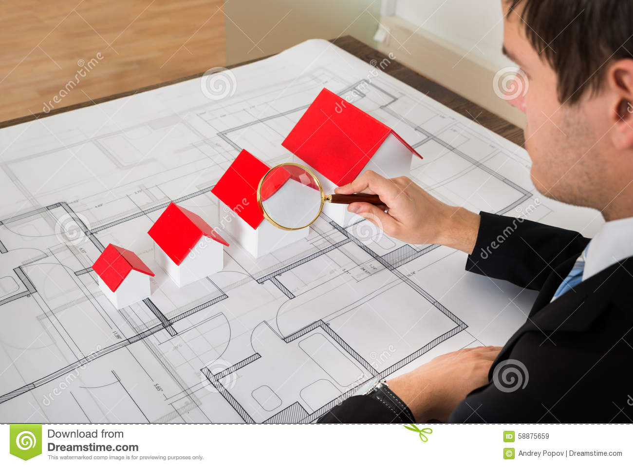 architect looking at house models through magnifying glass. Black Bedroom Furniture Sets. Home Design Ideas
