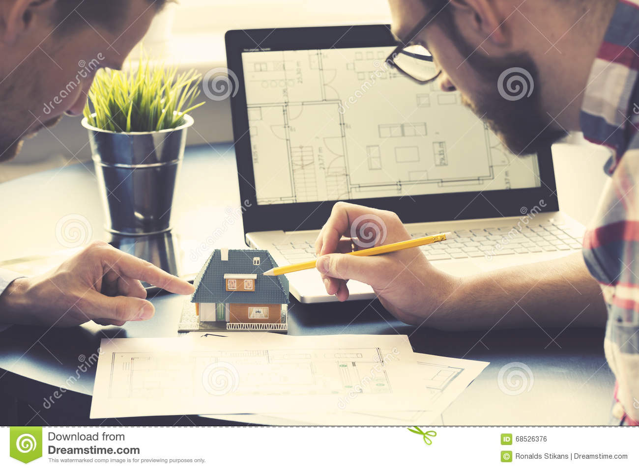 Architect showing new house model to customer at office