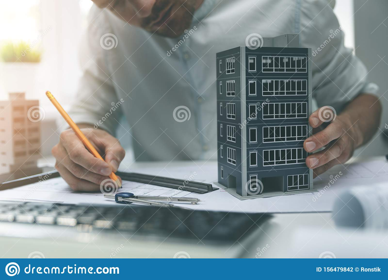 Architect working with new apartment building scale model in office