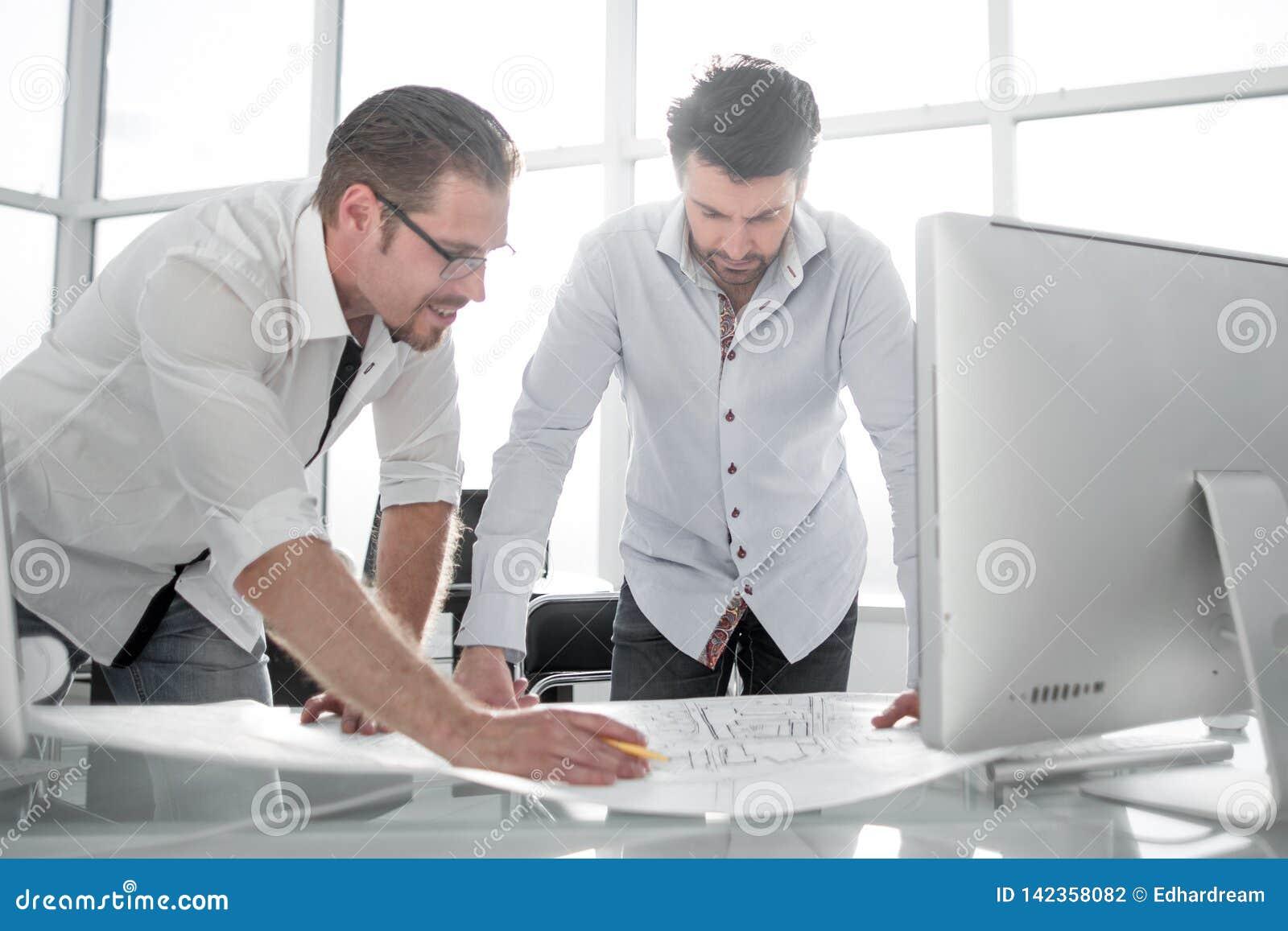 Architecte deux travaillant avec des modèles pour le plan architectural