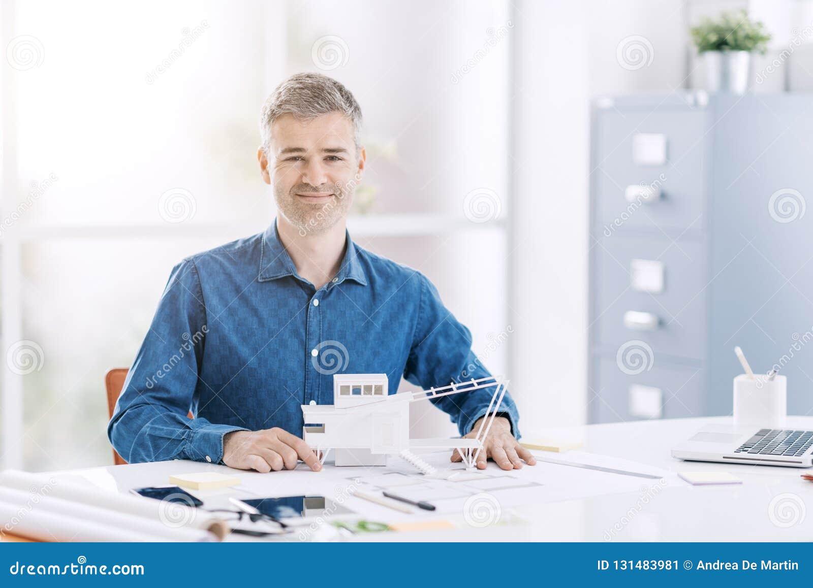 Architecte professionnel posant dans le bureau avec un modèle architectural d un bâtiment contemporain
