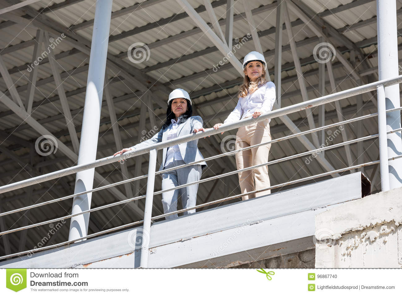 Architects in formal wear looking at camera while standing at construction site