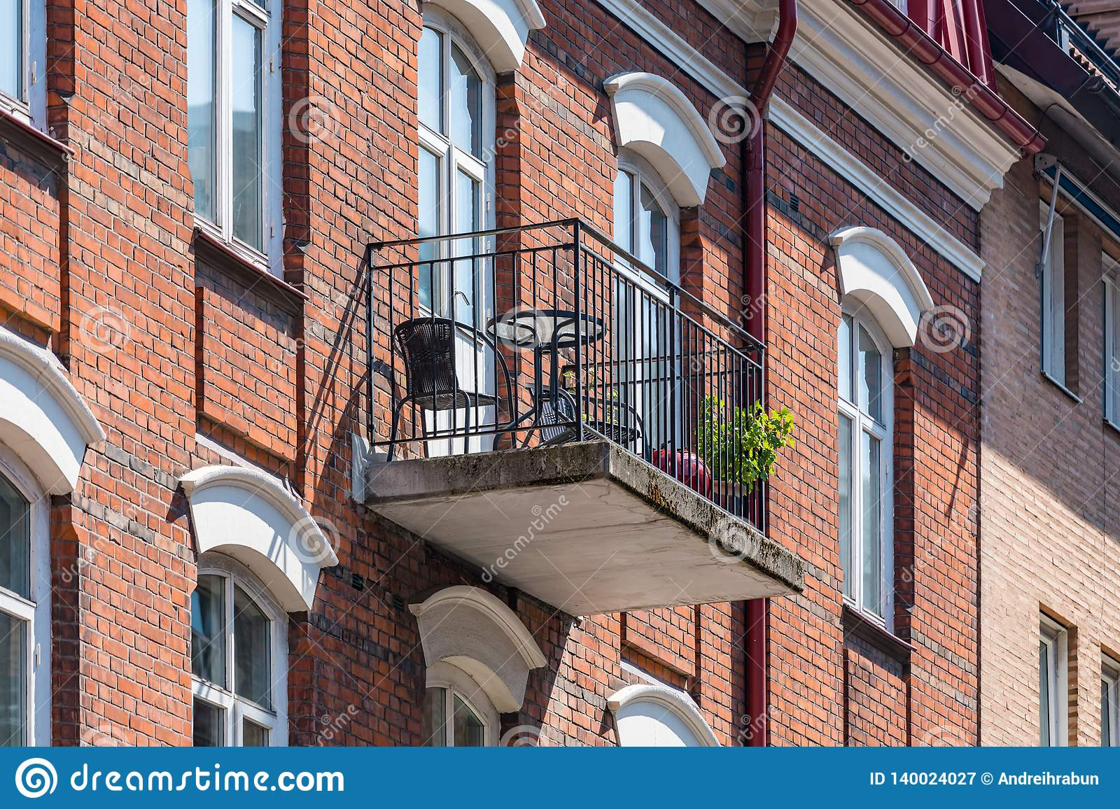 Architectural details of modern apartment building. Balcony with chairs and flowers