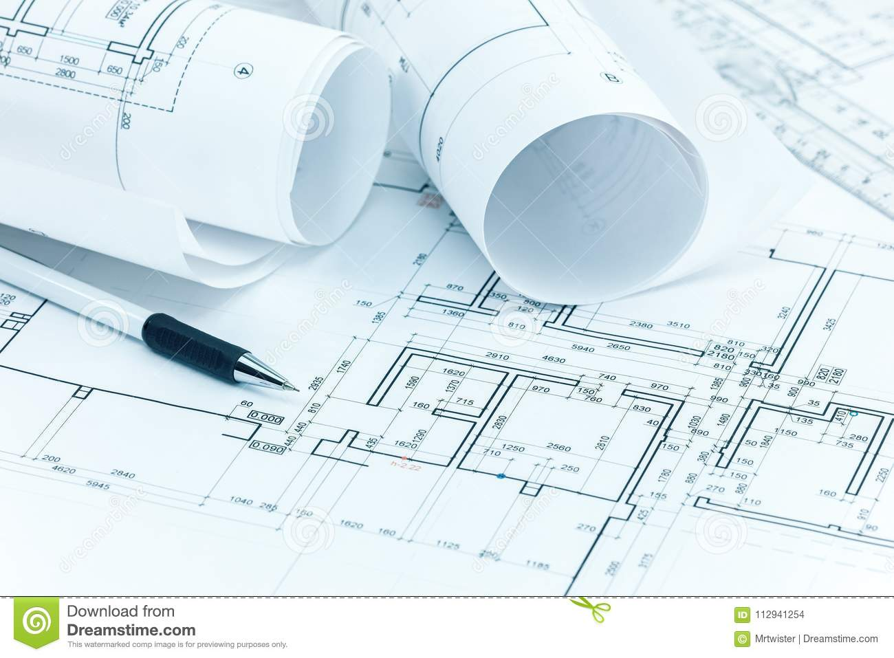 Architectural project plans, blueprint rolls, pencil and ruler o