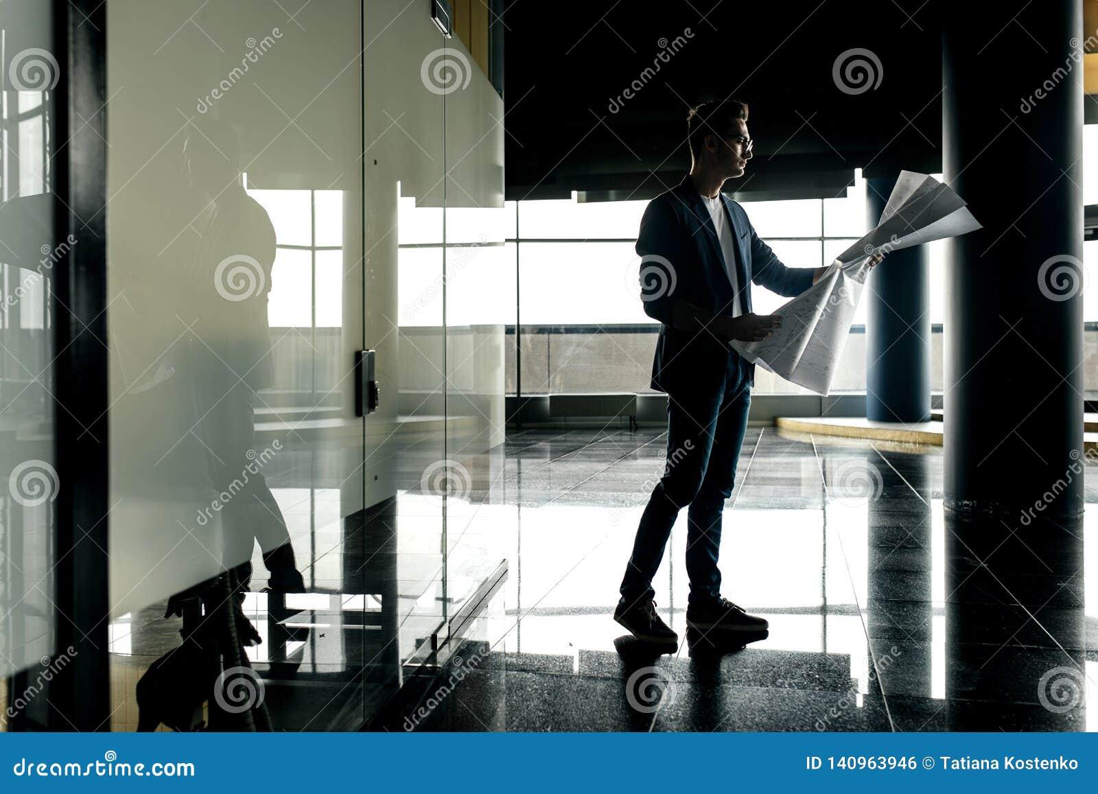Architekt w eleganckim odziewa chwyty ciąć na arkusze z rysunkiem w jego ręce i rozmowami telefonem na tle nowożytny szkło