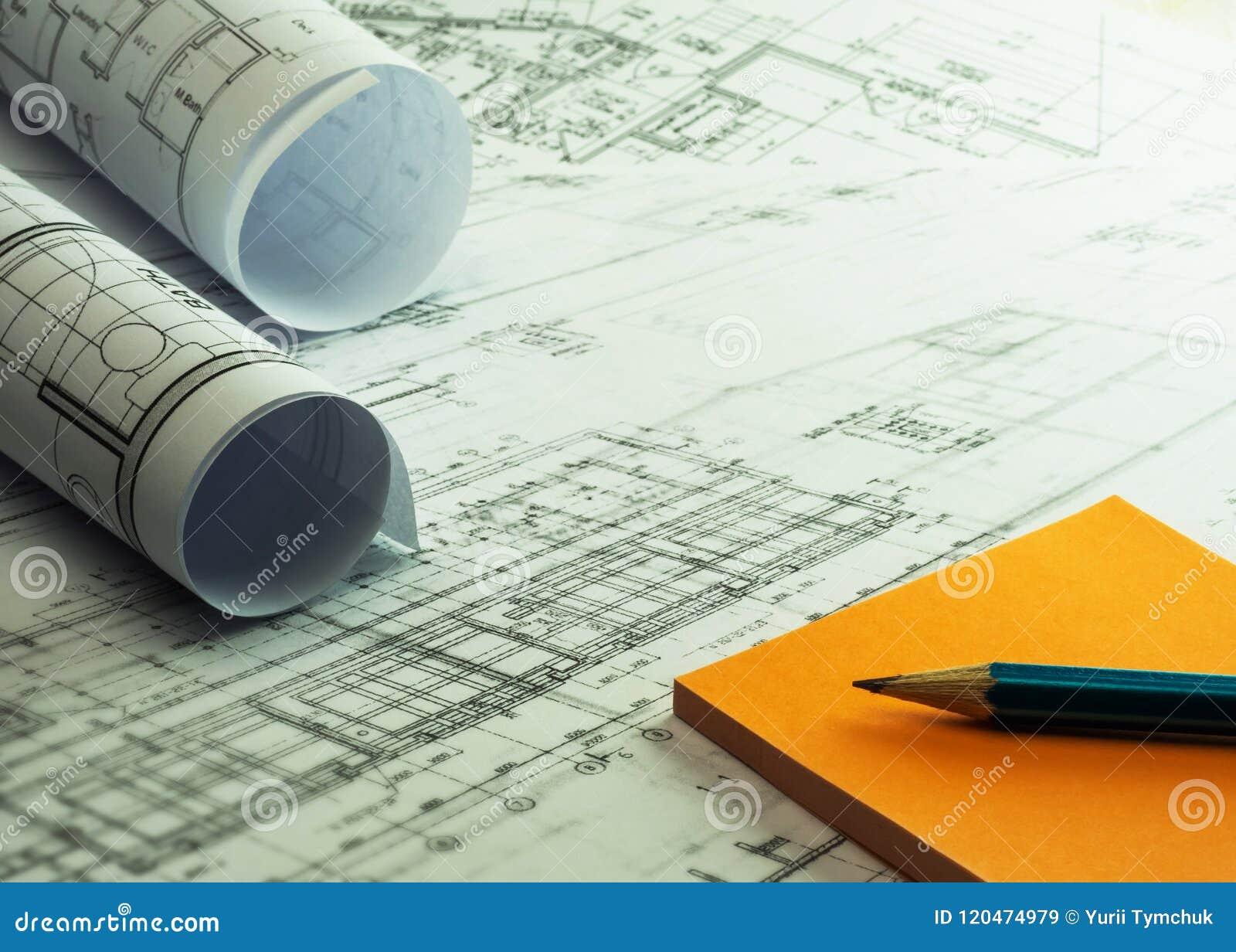 Architektenrollen und -pläne mit orange klebrigen Anmerkungen und Bleistift A
