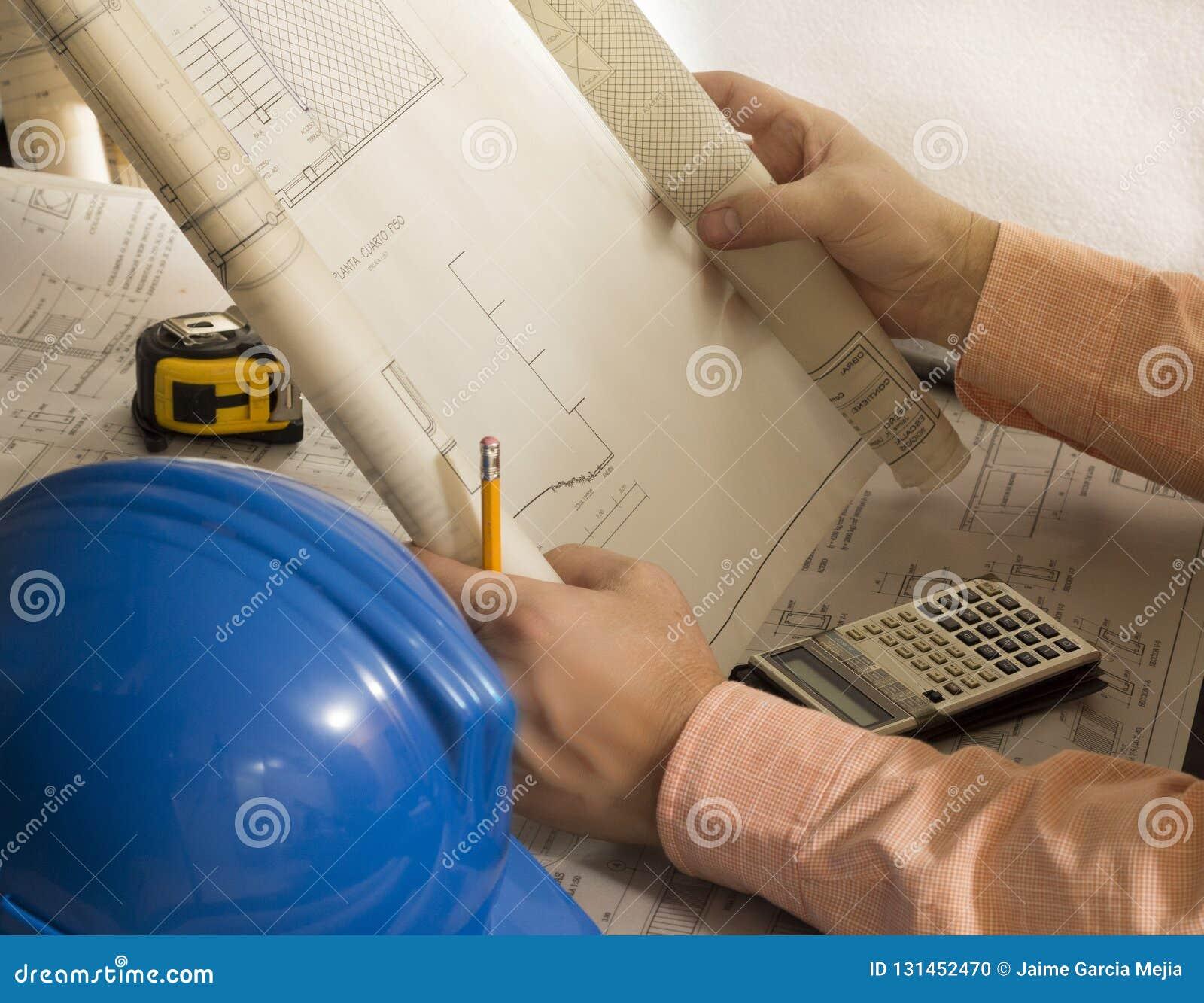 Architekturpläne des Bauingenieurarchitekten Pläne mit Meter, Sturzhelm, Taschenrechner und Bleistift wiederholend