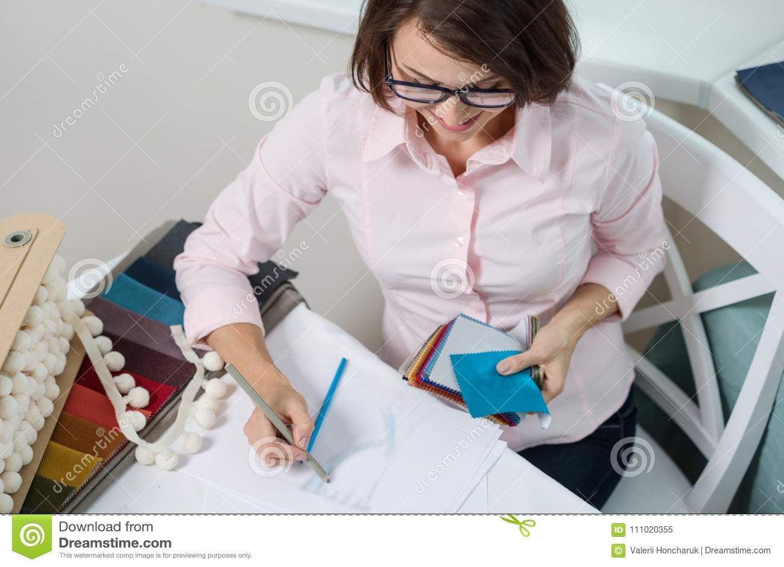 Architetto arredatore della donna, impianti con i campioni dei tessuti per le tende e ciechi