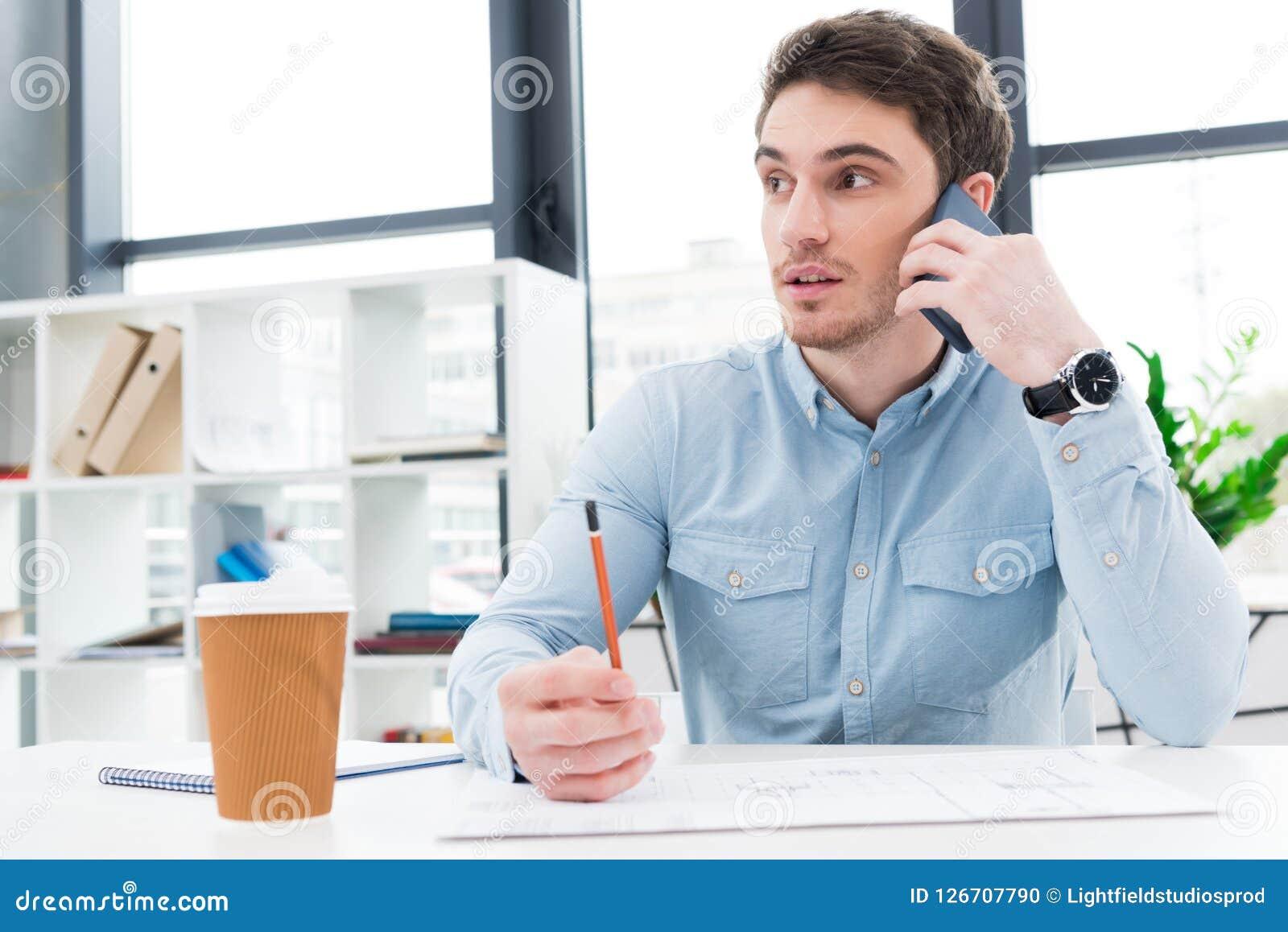 Architetto maschio che lavora con il modello e che parla sullo smartphone