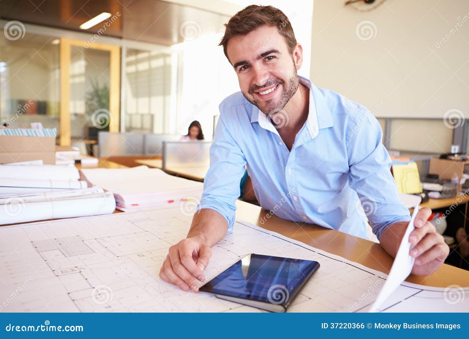 Architetto maschio with digital tablet che studia i piani for Ufficio architetto design