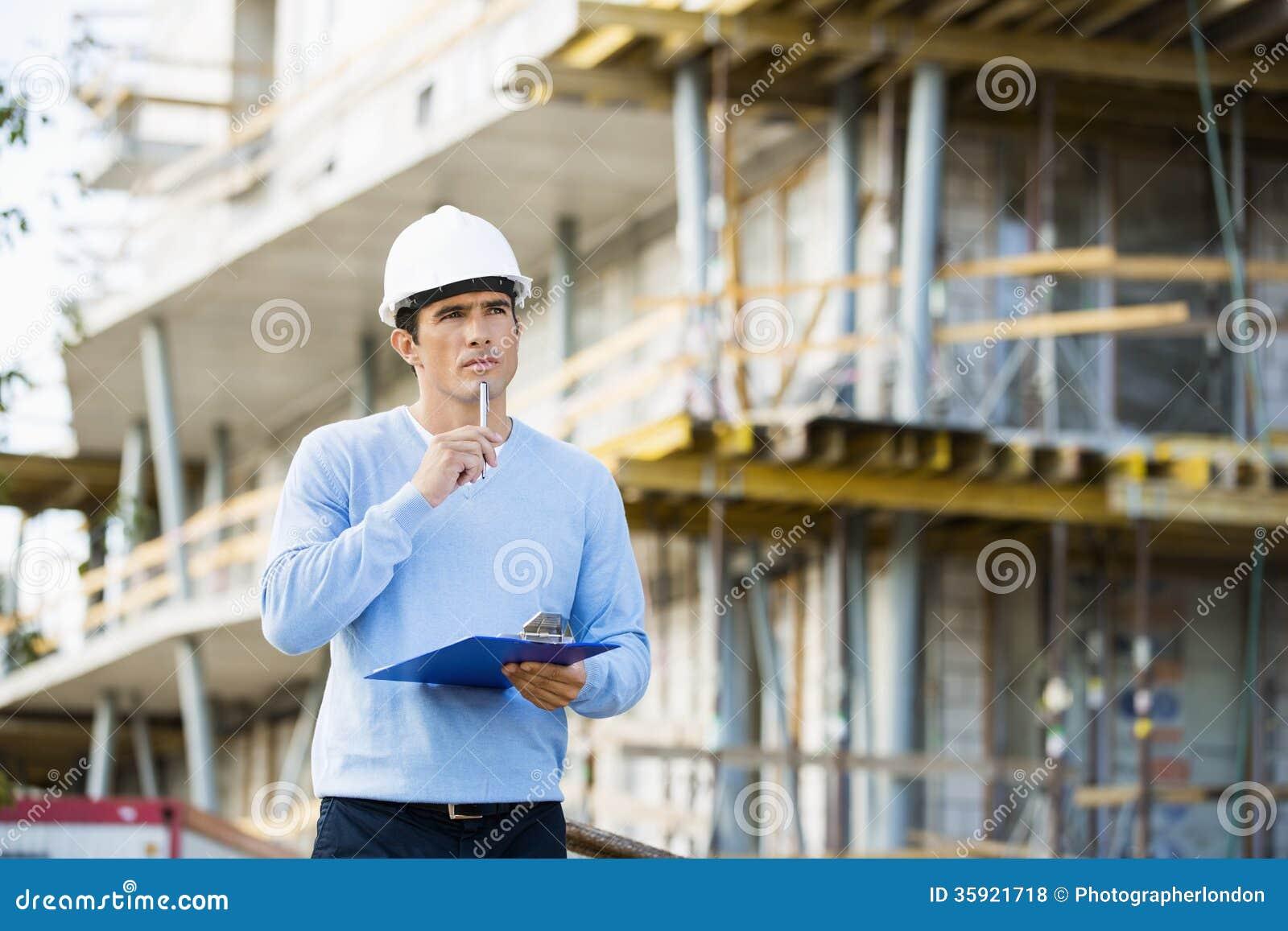 Architetto premuroso con la lavagna per appunti e penna che sta al sito
